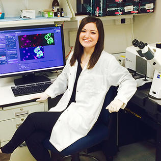 Stahl, in white lab coat, sits in front of computer monitor, next to microscope.