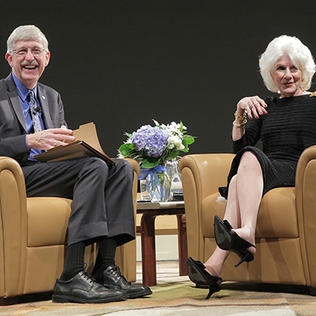 Collins and Rehm, seated on stage, smile as they interact with the audience.