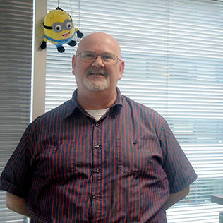Alastair Thomson in his office with a minion balloon behind him