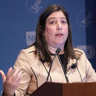 Houry at the podium at NIH
