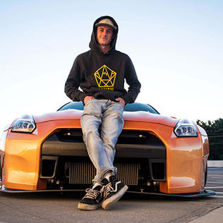 Andrew Lee poses in front of his bright orange Nissan GTR
