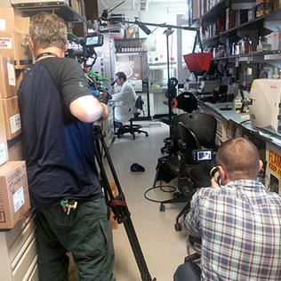 Man seated in lab coat at microscope as seen from behind two cameramen