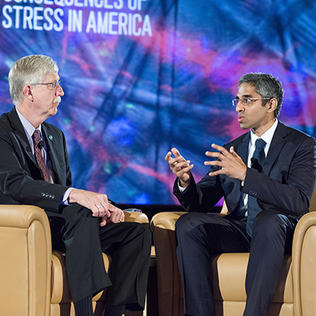 Dr. Collins and Dr. Murthy, seated on stage
