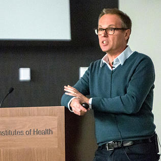 Dr. Gero Miesenböck lectures at a podium.