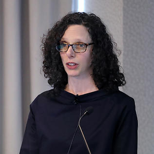 Alisa Roth speaks at podium in Neuroscience Center