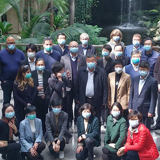 Group shot of people wearing masks covering nose and mouth.