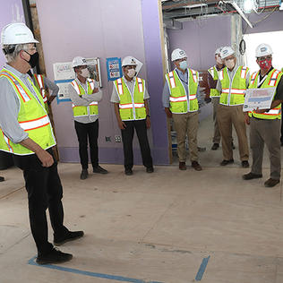 About a dozen people in helmets, masks, and safety vests stand in an unfinished room as one speaks.