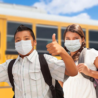 Three Latino kids, wearing backpacks and smiling behind their masks, give thumbs up - in front of a school bus with a bright blue sky overhead.
