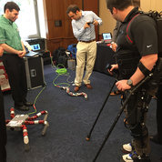 From health-focused exoskeletons to modular snakes. At the 2016 National Robotics Initiative briefing, participants (from l) Simon Kalouche and Alexander Ansari (Carnegie Mellon University) and Ryan Reese (Ekso Bionics) demonstrate their co-robots. PHOTO: JOE BALINTFY, SAARAA FAROOQ