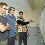 NINDS post-baccalaureate fellow Alec Calac joins colleagues at a poster session. PHOTO: ERNIE BRANSON