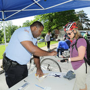 Cpl. Brett Alexander, community policing coordinator with the NIH Police, registers a bicyclist at BTWD. PHOTO: BILL BRANSON