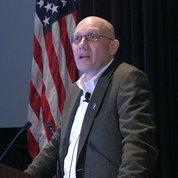 Rosenstein stands at podium