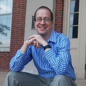 A smiling Eric Dishman sits outside Bldg. 1.