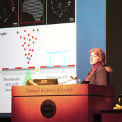 West at the NIH podium with slide projected beside her
