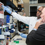 "In Sullivan's 2nd floor laboratory, Coons chats with Dr. Sabue Mulangu. ""I was explaining to the senator how in the laboratory we evaluate the antibody responses of human volunteers to Ebola vaccines,"" said Mulangu. ""We use an ELISA plate where Ebola purified glycoprotein is coated on the wells of the plate. We added a serial dilution of sera from vaccinated individuals. After different incubation times with laboratory reagents, we will observe the development of color in each well. The darker the color, the greater the amount of antibodies present in the serum."" PHOTO: CHIA-CHI CHARLIE CHANG"