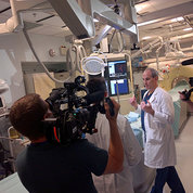A TV cameraman points video camera at Dr. Wood in a testing room in the Clinical Center