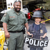 MPO Brian Sims poses with a young man trying on riot gear. PHOTO: CHIA-CHI CHARLIE CHANG