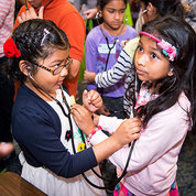 Two young girls listen to each other's heartbeat with stethoscopes