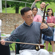 Dr. Xiaobin Guan of NHGRI plays the erhu, a two-string Chinese instrument.  PHOTO: KATIE CHAN