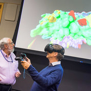 Wearing virtual reality goggles, Gates explores key immunologic epitopes of an influenza H1 hemagglutinin molecule, used to target next generation influenza vaccines, color coded to show the binding footprints of a set of broadly neutralizing antibodies (yellow), as well as several glycosylation sites (red). On his left is Dr. Phil Cruz, a structural biologist in NIAID's Office of Cyberinfrastructure and Computational Biology. PHOTO: LISA HELFERT