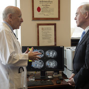 NCI's Dr. Steven Rosenberg discusses his research with Price. PHOTO: CHRIS SMITH