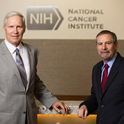 Schiller, Lowy stand in front of National Cancer Institute sign.