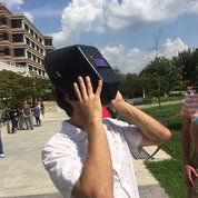 Brad Davidson, a fellow in NHGRI's Medical Genetics Branch, views the solar eclipse at its peak using a welding mask. PHOTOS: MARLEEN VAN DEN NESTE, RICH MCMANUS, CARLA GARNETT, DANA TALESNIK, CHILDREN'S INN