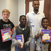In the Grammar Game Show sponsored by the NIH Executive Secretariat, victors include kids (from l) Sam Sky, age 10, whose dad is Yuri Sky of DPCPSI; and the grandsons of OD's Leslie Twyman, Chris Heath, age 9 and Kevin Heath III, age 10. The contestants won word search puzzle books for participating. Also shown is game show host Daryl Flood of ES. Game format, modeled after the television show It's Academic, posed grammar-related questions. Sam won 1st place, Kevin was 2nd and Chris was 3rd. PHOTO: MARLYCE GREEN