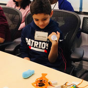 """Zak Elsafy displays a bionic device. His brother, Ramy, 14, wrote about it in a brief essay as part of an NICHD activity on being a reporter: """"My little brother put an electrode on his wrist…when he made a fist, the electrical signal in his muscle traveled through a circuit board and sent a pulse to the presenter Dr. Jennifer Jackson's arm, making her hand twitch."""" PHOTO: CHIA-CHI CHARLIE CHANG"""