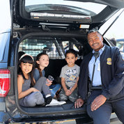 Cpl. Charles Abbington sits in the back of police SUV with youngsters. PHOTO: CHIA-CHI CHARLIE CHANG