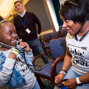 A child uses a stethoscope to listen to her heart while her mother looks on. PHOTO: LISA HELFERT