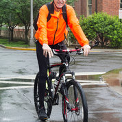 NIH director Dr. Francis Collins bicycles onto campus for a rainy Bike to Work Day 2018. PHOTO: MARLEEN VAN DEN NESTE
