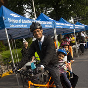 Dr. Prashant Chittiboina of NINDS's Surgical Neurology Branch rides in on his electric cargo bike with his kids. PHOTO: LISA HELFERT
