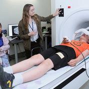 NIMH postbac fellow Gabrielle Reimann prepares Zorin Petrow for a mock MRI scan. PHOTO: CHIA-CHI CHARLIE CHANG