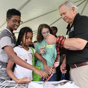 Ray Bosmans (r) lets kids touch his pet Honduran milksnake at Earth Day event. PHOTO: CHIA-CHI CHARLIE CHANG
