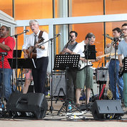 The Affordable Rock 'n Roll Act Band performs behind Bldg. 10 at the end of the festival. They include (from l) Dr. Scott Durum, NCI (with sax); Laura Chopp, NCI; Dr. John Tisdale, NHLBI; Quino Maduro, NHGRI; Cecelia Tamburro (obscured), NHGRI; NIH director Dr. Francis Collins; Dr. Peter Grayson, NIAMS; Dr. Michael Lenardo, NIAID; Dr. Will Sears, NIAID (fiddle); Dr. Mike Pazin, NHGRI (unseen on drums, behind Sears); Dr. Ivan Vujkovic-Cvijin, NIAID; and Dr. John O'Shea, NIAMS. PHOTO: CHIA-CHI CHARLIE CHANG