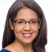 A smiling Patricia Valdez wearing a blue shirt.