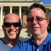 Chris and Jason Plummer smile as they pose in front of Bldg. 1 on NIH's campus.