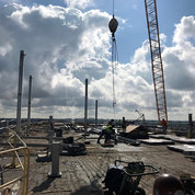 Workers receive the dunnage steel on the roof for assembly. The dunnage was installed to support mechanical equipment and large piping.