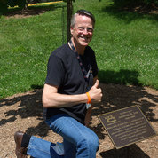 Bruce Lee poses by the tree, on the Clinical Center's south lawn, planted in his son Andrew's memory. PHOTO: DANA TALESNIK