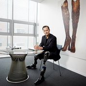 Herr is smiling, seated at a table. His prosthetic legs are prominent. On a wall behind him is an artwork of a pair of legs.