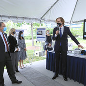 Tromberg stands in front of a display table and speaks to several senators under a tent